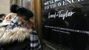 FILE - In this Jan. 2, 2019 file photo, women peer in the front door of Lord & Taylor's flagship Fifth Avenue store which closed for good, in New York. A slew of once-beloved brands from Lord & Taylor to Ann Taylor have filed for Chapter 11 since the pandemic. (AP Photo/Kathy Willens, File)