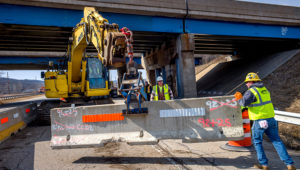 A Halverson Construction Co. crew guides a concrete barrier into place on Monday along southbound Illinois Route 116 at its intersection with U.S. Route 24 in East Peoria. | DAVID ZALAZNIK/JOURNAL STAR