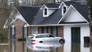 Water from the Pearl River floods this northeast Jackson, Miss., home and car, Sunday, Feb. 16, 2020. (AP Photo/Rogelio V. Solis)