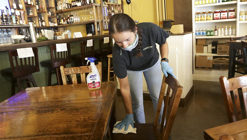 Carlee Packard wipes down a table and chairs after customers finished eating at Puckett's Grocery & Restaurant Monday, April 27, 2020, in Franklin, Tenn. (AP Photo/Mark Humphrey)