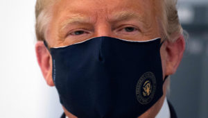 In this file photo US President Donald Trump wears a mask as he tours a lab where they are making components for a potential vaccine at the Bioprocess Innovation Center at Fujifilm Diosynth Biotechnologies in Morrisville, North Carolina on July 27, 2020. (Photo by JIM WATSON / AFP)