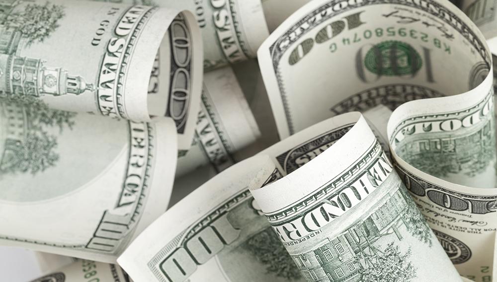 Pile of United States dollar USD banknotes.   Photo: Eugene Sergeev