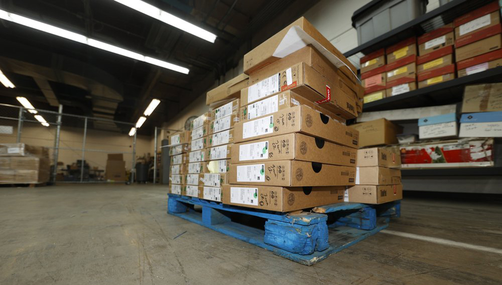 A handful of Lenovo Chromebook laptops sit in shipping boxes in an empty warehouse used for distribution by Denver Public Schools, Friday, Aug. 21, 2020, in Denver. (AP Photo/David Zalubowski)