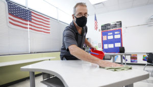 FILE - In this July 29, 2020, file photo, custodian Doug Blackmer cleans a desk in a classroom at the Jesse Franklin Taylor Education Center in Des Moines, Iowa. (AP Photo/Charlie Neibergall, File)
