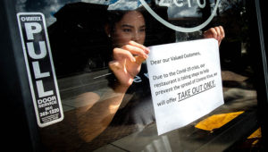 Supervisor Kryztel Natividad posts a notice on the door of Zero X, a coffee and tea cafe in Riverside on Tuesday, March 17, 2020, to tell customers of a disruption in service due to the novel coronavirus. (Photo by Watchara Phomicinda, The Press-Enterprise/SCNG)