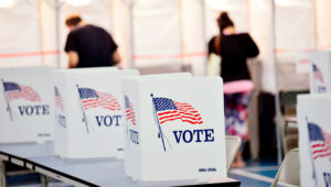 In this Sept. 8, 2020 photo, voting booths are kept socially distant at the Chesterfield, N.H. polling site. A majority of President Donald Trump's supporters plan to cast their ballot on Election Day, while about half of Joe Biden's backers plan to vote by mail. (Kristopher Radder/The Brattleboro Reformer via AP)