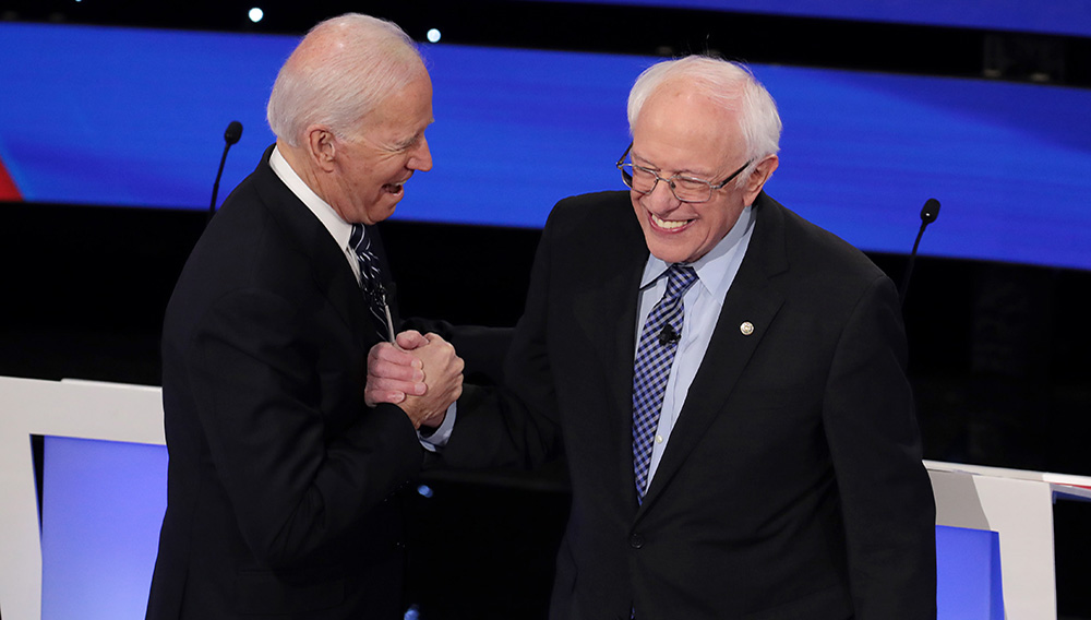 Former Vice President Joe Biden (L) greets Sen. Bernie Sanders (I-VT) before the Democratic presidential primary debate at Drake University on January 14, 2020 in Des Moines, Iowa. | Scott Olson / Getty Images