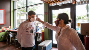 A Soupergirl employee gets his temperature checked before entering the restaurant. | Courtesy: Soupergirl