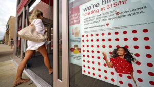 FILE - In this Sept. 2, 2020, file photo, a help wanted sign hangs on the door of a Target store in Uniontown, Pa. Hundreds of thousands of Americans likely applied for unemployment benefits last week, a high level of job insecurity that reflects economic damage from the coronavirus outbreak. (AP Photo/Gene J. Puskar, File)
