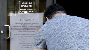 FILE - In this March 26, 2020 file photo a man takes a photo of a sign advising that the Employment Development Department is closed due to coronavirus concerns, in San Francisco. (AP Photo/Jeff Chiu, File)