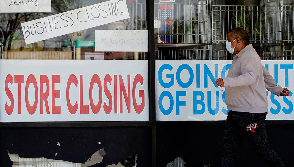 A man walks by stores in Niles, Ill. The Commerce Department released data Thursday showing that second-quarter gross domestic product plunged by 9.5 percent, the fastest drop in modern record-keeping. (Nam Y. Huh/AP)