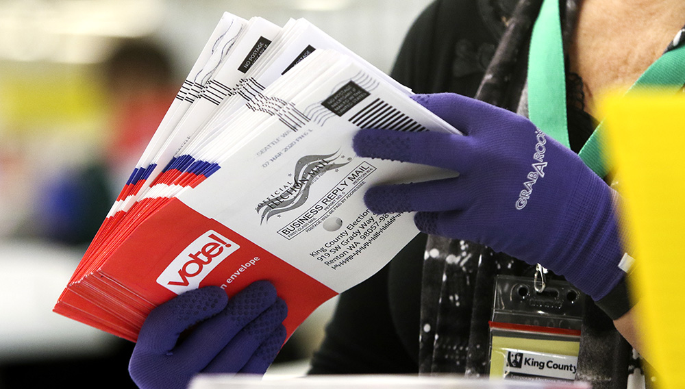 An election worker sorts vote-by-mail ballots for Washington state's presidential primary on March 10 in Renton, a suburb of Seattle. | Photo: Jason Redmond