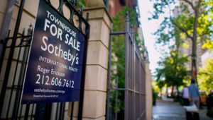 """A Sotheby's """"For Sale"""" sign is displayed outside of a townhouse in New York, U.S., on Monday, June 23, 2014. 
