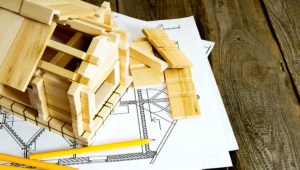 Building house. House construction. Many drawings for building and wooden house on old wooden background. | SarapulSar38/istockphoto