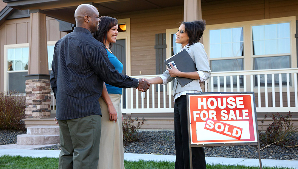 Couple Shakes Hands With Realtor Outside New House.   freeimages.com