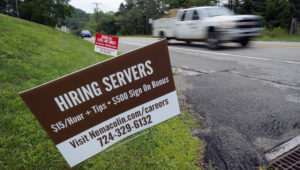 FILE - In this Wednesday, Sept. 2, 2020, file photo help wanted signs for servers and cooks at Nemacolin Woodlands Resort and Spa are displayed along route 40 at the entrance to the resort in Farmington, Pa. U.S. employers advertised more jobs but hired fewer workers in July, sending mixed signals about a job market in the wake of the coronavirus outbreak. (AP Photo/Gene J. Puskar, File)