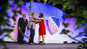 In this July 14, 2016 photo Democratic presidential candidate Hillary Clinton, accompanied by then-LULAC President Roger C. Rocha, Jr., left, hugs University of Texas student Dreamer Lizeth Urdiales, right, as she arrives to speaks at the 87th League of United Latin American Citizens National Convention at the Washington Hilton in Washington. (AP Photo/Andrew Harnik, File)