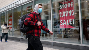 A passer-by walks past a store closing sign, right, in the window of a department store, Tuesday, Oct. 27, 2020, in Boston. Americans may feel whiplashed by a report Thursday, Oct. 29, on the economy's growth this summer, when an explosive rebound followed an epic collapse. (AP Photo/Steven Senne)