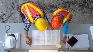 Top view of group of engineering team is meeting, planning construction work, looking paper plans at construction site,overhead view,Concept for team work. | Photo: PITIPHAT57/Getty Images