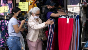 A woman shops at a clothing store, Friday, Sept. 25, 2020, in New York. U.S. consumer spending slowed in August and personal income fell as a $600 weekly benefit for Americans who are unemployed during the pandemic expired. (AP Photo/Mark Lennihan)