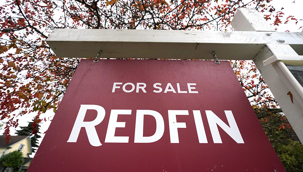 """A Redfin """"for sale"""" sign stands in front of a house Wednesday, Oct. 28, 2020, in Seattle. Several fair housing organizations accused Redfin of systematic racial discrimination in a lawsuit Thursday. (AP Photo/Elaine Thompson)"""
