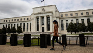 A woman walks past the U.S. Federal Reserve building in Washington D.C., May 21, 2020. | Ting Shen | Xinhua News Agency | Getty Images