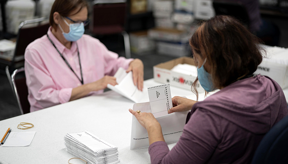 FILE - In this July 29, 2020, file photo, Lisa Finander, right, checks that each ballot has the voter's name on the ballot and mailing envelope and Laurie Mattila, left, checked that it was correct at Minneapolis Elections & Voter Services in Minneapolis. (Glen Stubbe/Star Tribune via AP, File)