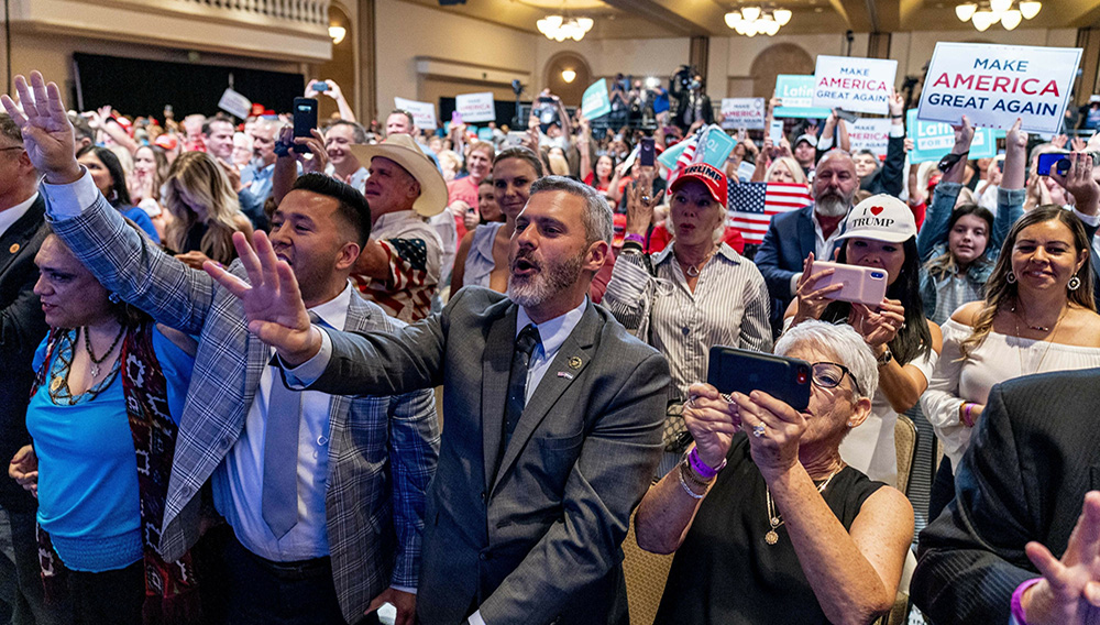 FILE - In this Sept. 14, 2020 file photo, supporters react as President Donald Trump speaks at a Latinos for Trump Coalition roundtable at Arizona Grand Resort & Spa in Phoenix. President Donald Trump is putting up a fight for Latino voters in key swing states with Democratic candidate Joe Biden. (AP Photo/Andrew Harnik)