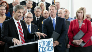 This Monday, Oct. 7, 2019 file photo, Ohio Sen. Matt Dolan, left, speaks during a news conference at the Ohio Department of Public Safety in Columbus, Ohio. Dolan says, Thursday, Oct. 1, 2020, an aid package for small businesses and people struggling to pay rent during the coronavirus pandemic is coming soon. (Joshua A. Bickel, The Columbus Dispatch via AP, File)