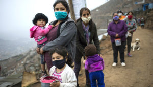 FILE - In this June 17, 2020, file photo, people wearing masks to curb the spread of the new coronavirus wait in a line for a free meal at the Villa Maria del Triunfo district in Lima, Peru. (AP Photo/Rodrigo Abd, FIle)