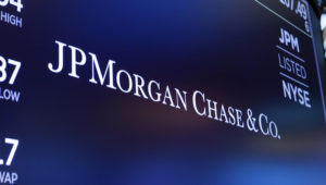 FILE - In this Aug. 16, 2019, file photo, the logo for JPMorgan Chase & Co. appears above a trading post on the floor of the New York Stock Exchange in New York. (AP Photo/Richard Drew, File)