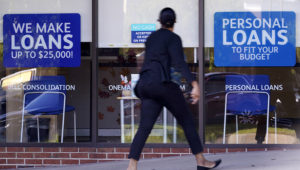 A woman walks past a personal finance loan office Thursday, Oct. 1, 2020, in Franklin, Tenn. Consumers, by and large, improved their credit profile during the pandemic. (AP Photo/Mark Humphrey)