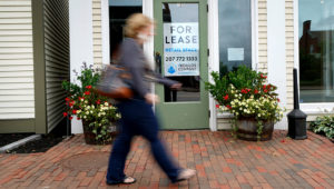FILE - In this Sept. 2, 2020, file photo, a shopper walks by one of several vacant retail spaces among the outlet shops in Freeport, Maine. The U.S. unemployment rate dropped to 7.9% in September, but hiring is slowing and many Americans have given up looking for work, the government said Friday, Oct. 2, in the final jobs report before the voters decide whether to give President Donald Trump another term. (AP Photo/Robert F. Bukaty, File)