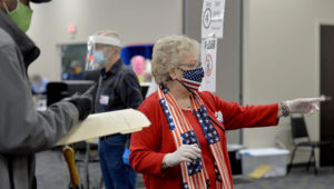 Election judge Janice Stone directs voters to the ballot box during the first day of in-person early voting at the Washington County Election Center in Hagerstown, Md., Monday, Oct. 26, 2020. (Colleen McGrath/The Herald-Mail via AP)