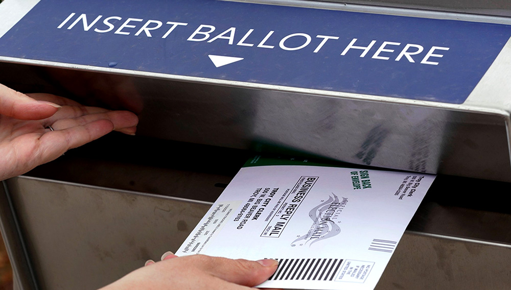 FILE - In this Thursday, Oct. 15, 2020, file photo, Nikki Schueller inserts her absentee voter ballot into a drop box in Troy, Mich. Just days before the presidential election, millions of mail-in ballots have still not been returned in key battleground states. (AP Photo/Paul Sancya, File)