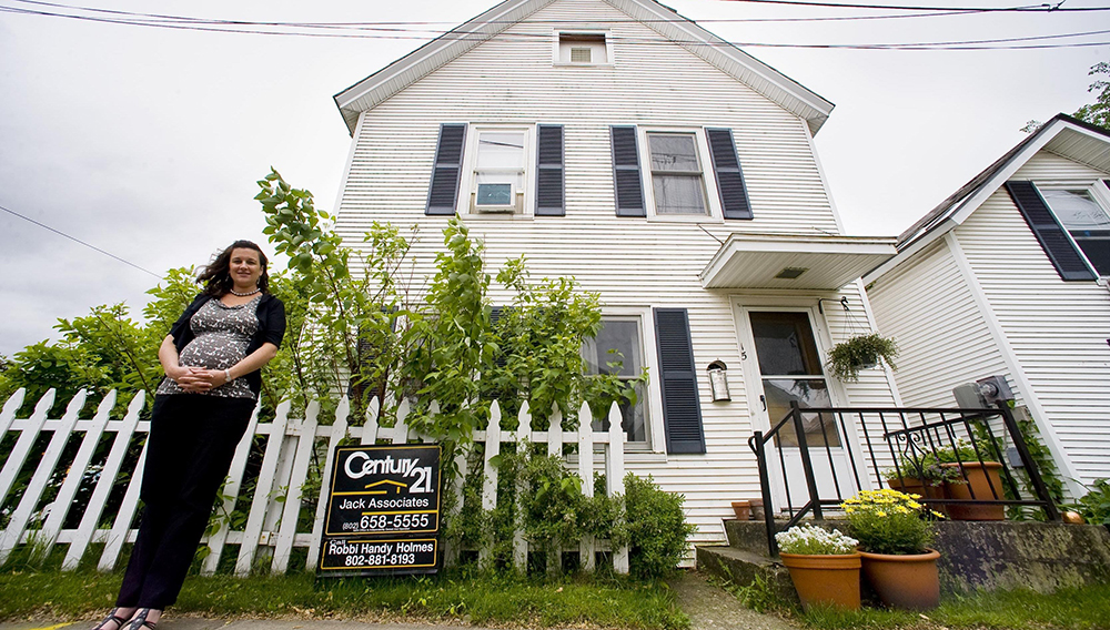 Maura Collins of the Vermont Housing Finance Authority next to a home for sale in Burlington in this file photo from 2011. | Glenn Russell/Free Press