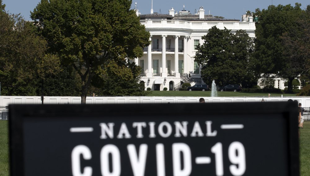The White House is seen in the background as sign of the National COVID-19 Remembrance, event at The Ellipse outside of the White House, Sunday, Oct. 4, 2020, in Washington. (AP Photo/Jose Luis Magana)