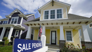 """In this Friday, Sept. 25, 2020 photo, a """"sale pending"""" sign is posted on.a home in Westfield, Ind. Sales of existing homes climbed 9.4% in September, the National Association of Realtors said Thursday, the latest sign that the housing market remains red hot despite the coronavirus pandemic. (AP Photo/Michael Conroy)"""