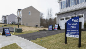 Model homes and for sale signs line the streets as construction continues at a housing plan in Zelienople, Pa., Wednesday, March 18, 2020. Sales of new homes fell by 3.5% in September to a seasonally-adjusted annual rate of 959,000 million units. (AP Photo/Keith Srakocic)