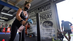 Giannina Nicoletti sanitizes a piece of equipment as she works out, Monday, Aug. 31, 2020, at Legacy Fit in the Wynwood Art District of Miami. As the vast majority of in-person fitness clubs switched to virtual classes when the pandemic hit, Legacy Fit took the opposite approach. (AP Photo/Wilfredo Lee)