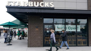"""Customers walk past a sign that reads """"We're Open!"""" at a Starbucks Coffee store in south Seattle, Tuesday, Oct. 27, 2020. Starbucks saw faster-than-expected recovery in the U.S. and China in its fiscal fourth quarter, giving it confidence as it heads into the holiday season. (AP Photo/Ted S. Warren)"""