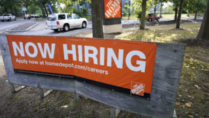 Vehicles drive past a now hiring sign as they enter a parking lot for a Home Depot store location, Wednesday, Sept. 30, 2020, in Boston. The number of Americans seeking unemployment benefits declined last week to a still-high 837,000, evidence that the economy is struggling to sustain a tentative recovery that began this summer. (AP Photo/Steven Senne)