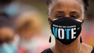 FILE PHOTO: A woman wears a mask with a message urging voter participation while she waits in line to enter a polling place on the first day of the state's in-person early voting for the general election in Durham, North Carolina, U.S. October 15, 2020. REUTERS/Jonathan Drake/File Photo