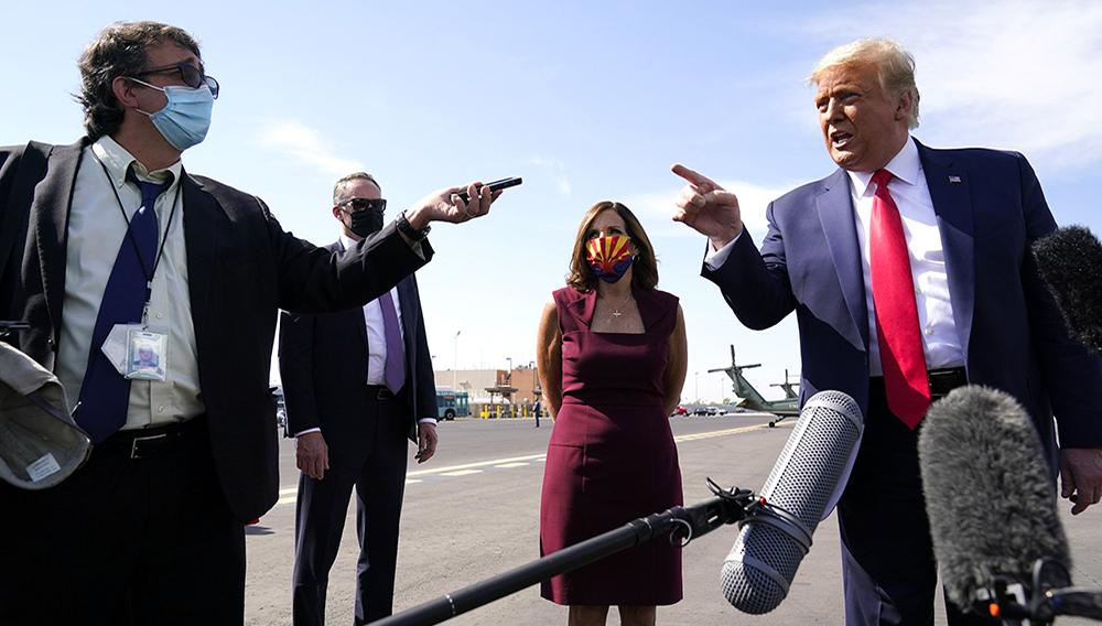 President Donald Trump talks to reporters at Phoenix Sky Harbor International Airport, Monday, Oct. 19, 2020, in Phoenix. Second from right is Sen. Martha McSally, R-Ariz. (AP Photo/Alex Brandon)
