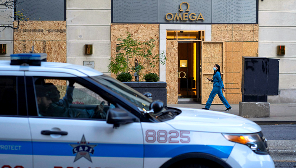 Plywood covers the windows of an Omega store in Chicago, Illinois, U.S. October 13, 2020. Chicago police have warned local retailers to prepare for possible protests around Election Day. REUTERS/Moe Zoyari