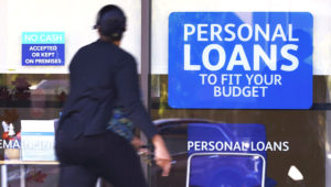 A woman walks past a personal finance loan office Thursday, Oct. 1, 2020, in Franklin, Tenn. U.S. consumers cut back on their borrowing in August, with credit card use dropping for a sixth straight month, reflecting caution in the midst of the pandemic-triggered recession. (AP Photo/Mark Humphrey)