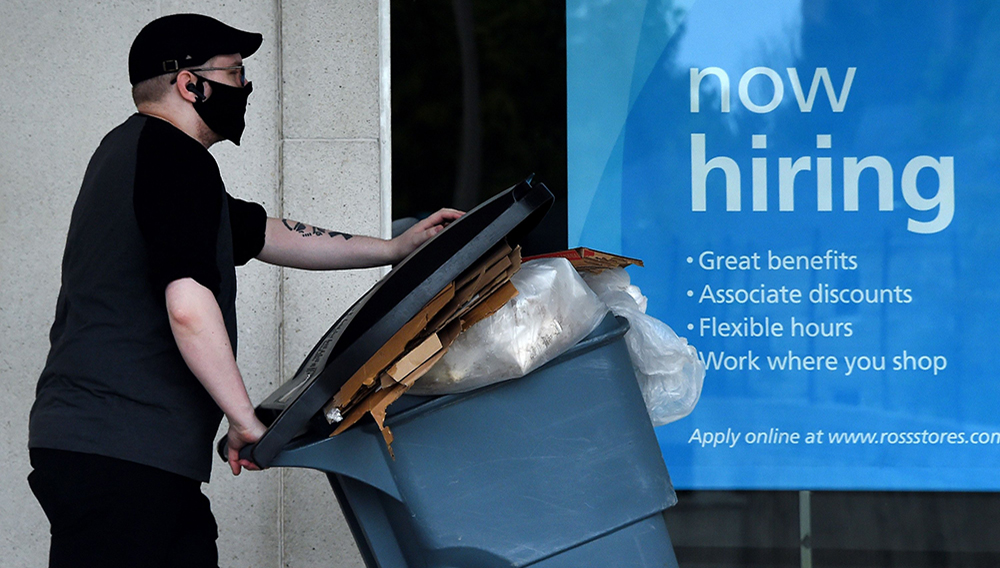 """A man wearing a face mask walks past a """"Now Hiring"""" sign in front of a store amid the coronavirus pandemic in Arlington, Virginia, U.S., May 14, 2020. (AFP Photo)"""