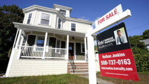 A for sale sign stands in front of a house, Tuesday, Oct. 6, 2020, in Westwood, Mass. U.S. long-term mortgage rates slipped this week as the key 30-year loan marked a new all-time low for the 11th time this year. (AP Photo/Steven Senne)