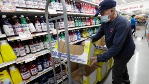 In this Wednesday, June 3, 2020 photo, Juan Santos stocks shelves at the Presidente Supermarket in the Little Havana neighborhood of Miami. (AP Photo/Wilfredo Lee)
