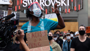 A New York nurse speaks to the crowd at a protest at Times Square. (Photo by Marrian Zhou)